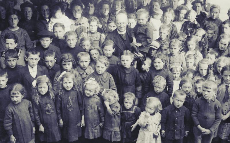 Henri Syoen, priester in Detroit, omring door vooral Oost-Vlaamse kinderen, oorlogsvluchtelingen uit België. De meesten van hen hadden al familie in de VS en maakten de oversteek na een bijzondere missie in bezet België. Detroit, augustus 1915 [ADVN, VFC 591]