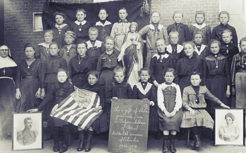 Tijdens de Eerste Wereldoorlog kwam vanuit de Verenigde Staten veel materiële hulp naar het zwaar getroffen België. Als teken van dankbaarheid werden later bijzondere klasfoto's verstuurd. Leerlingen van de meisjesschool van de zusters Crombeen in Onderdale (Ursel) poseerden in zondagse kledij met onder meer portretten van het Belgische vorstenpaar en de Amerikaanse vlag. Ursel, 1918 of 1919 [Collectie Herlinde Trenson / Erfgoedbank Meetjesland, PrHT_006]